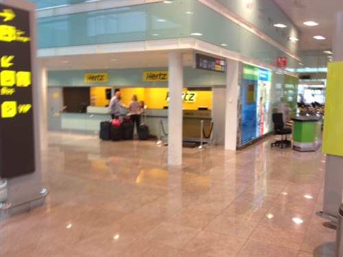 The yellow neon of the Hertz desk is clearly visible in Barcelona's Terminal 1 car hire arrivals area
